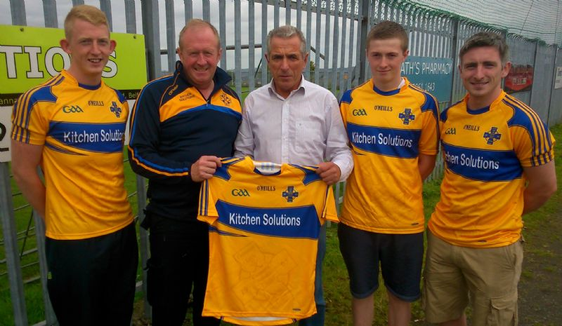 Gerard McFall from Kitchen Solutions presenting senior footballers with new kit.